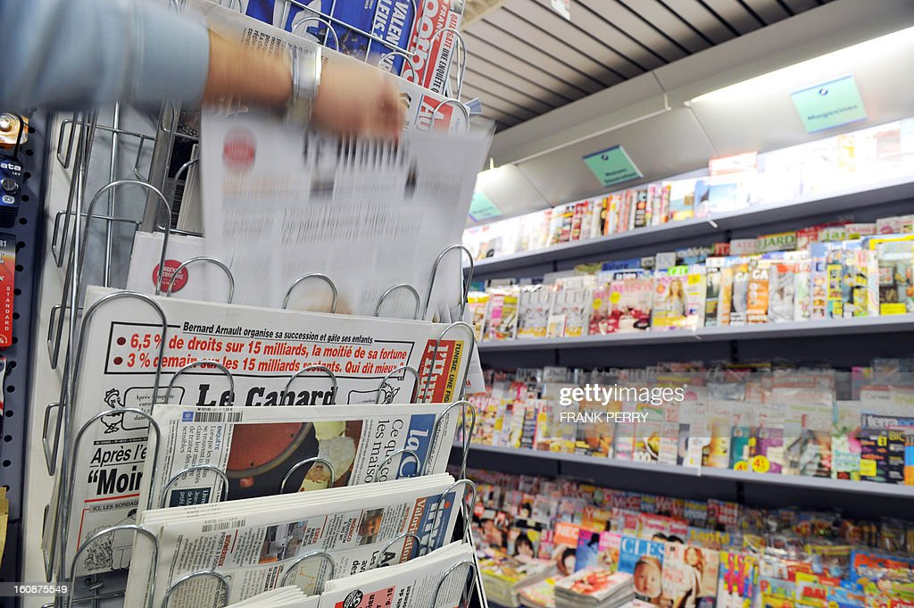 A vendor fills a newspapers stand in a bookshop on February 7, 2013 in Nantes, western France. AFP PHOTO FRANK PERRY