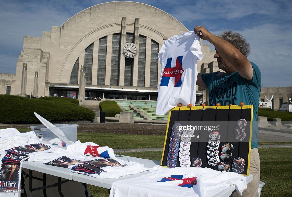 A vendor folds shirts for sale in front of the Cincinnati Museum Center at Union Terminal ahead of a campaign event with Hillary Clinton, former Secretary of State and presumptive Democratic presidential nominee, not pictured, in Cincinnati, Ohio, U.S., on Monday, June 27, 2016. Clinton released a new national television ad on Sunday attacking likely Republican rival Donald Trump for his comments on the U.K's decision to leave the European Union, and later warned of the negative impact that 'bombastic' behavior can have at times of crisis. Photographer: Ty Wright/Bloomberg via Getty Images