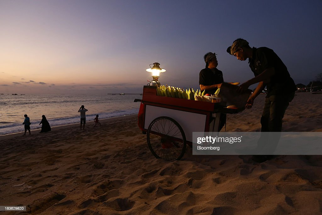 A vendor grills corns on a beach at dusk in Jimbaran, Bali, Indonesia, on Saturday, Oct. 5, 2013. Indonesia's central bank kept its key interest rate unchanged after its most aggressive tightening cycle in almost eight years as inflation pressure eased. Photographer: SeongJoon Cho/Bloomberg via Getty Images
