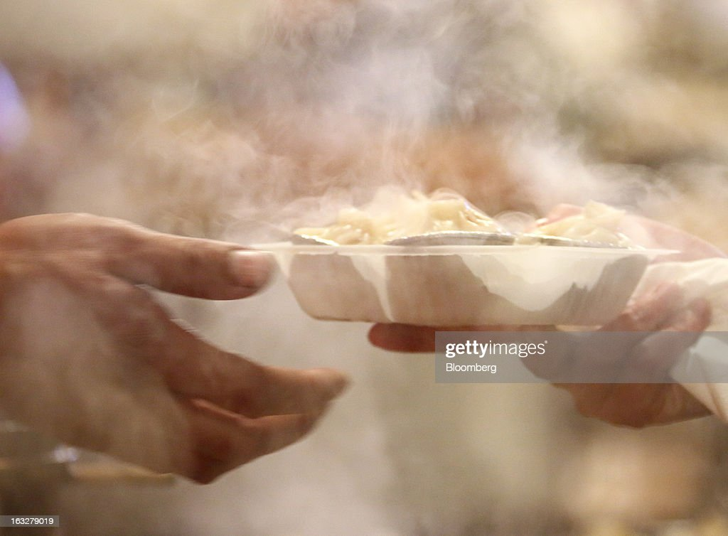 A vendor hands a dish of dumplings to a customer at a stall in a market at night in Beijing, China, on Wednesday, March 6, 2013. China maintained its economic-growth target at 7.5 percent for 2013 while setting a lower inflation goal of 3.5 percent, setting up a challenge for new leaders to keep prices in check without harming expansion. Photographer: Tomohiro Ohsumi/Bloomberg via Getty Images