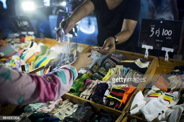 A vendor hands a onehundred Thai baht banknote and a bag of socks to a customer at a stall in the Jatujak Green night market known as the JJ Green...