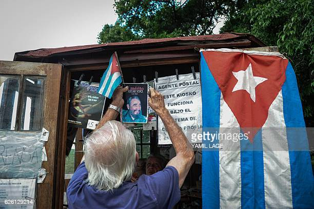 A vendor hangs a booklet with the image of Cuban revolutionary leader Fidel Castro at a kiosk in Havana on November 27 2016 two days after Castro's...