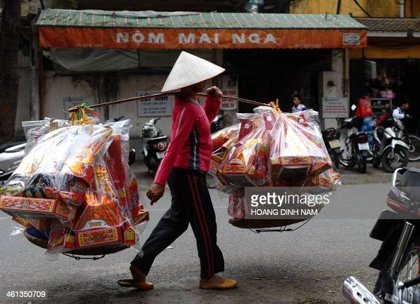 A vendor hawks votive paper along a street in downtown Hanoi on January 8 2014 Burning votive paper on the occasion of the Lunar New Year is a...