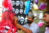 A vendor helps a customer with a wig sold at a roadside shop ahead of the Holi festival in Allahabad on March 15 2014 Holi the popular Hindu spring...