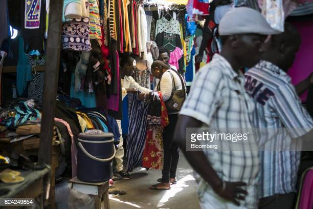 A vendor helps a customer with clothing at the Sandaga market in the Plateau district of Dakar Senegal on Friday July 28 2017 Senegalese voters will...