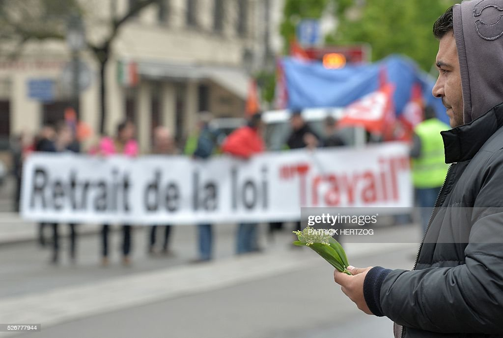 A vendor holds a bouquet of lily of the valley as participants hold a banner reading 'Withdrawal of the labour law' during the traditional May Day rally in Strasbourg, eastern France, on May 1, 2016. / AFP / PATRICK
