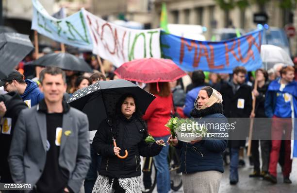 A vendor holds a bouquet of lily of the valley during the traditional May Day rally in Strasbourg eastern France on May 1 2017 / AFP PHOTO / PATRICK...