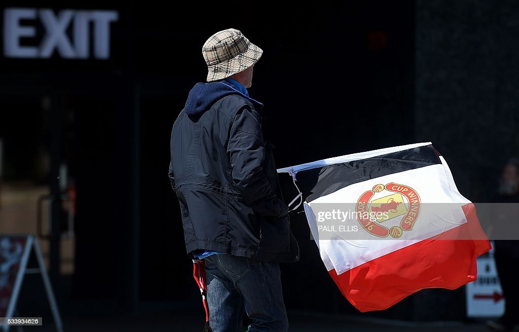 A vendor holds flags as he trys to sell merchandise outside Manchester United's Old Trafford football stadium in Manchester, north-west England on May 24, 2016. Jose Mourinho was on the verge of fulfilling his dream of managing Manchester United on Tuesday after Louis van Gaal's troubled two-year reign came to a bitter end. The path was clear for the former Chelsea manager to be confirmed as the new United boss after Van Gaal was sacked Monday -- the price of failing to get one of the world's biggest clubs into the Champions League. ELLIS
