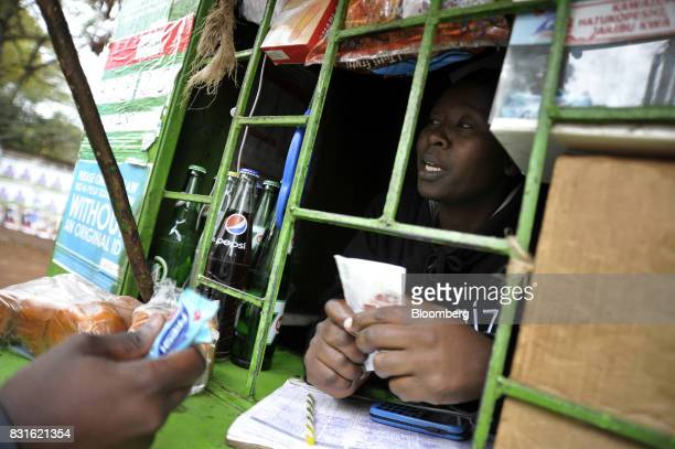 A vendor holds Kenyan shilling banknotes while serving a customer from her kiosk selling sweets and sodas in Nairobi Kenya on Tuesday Aug 15 2017...