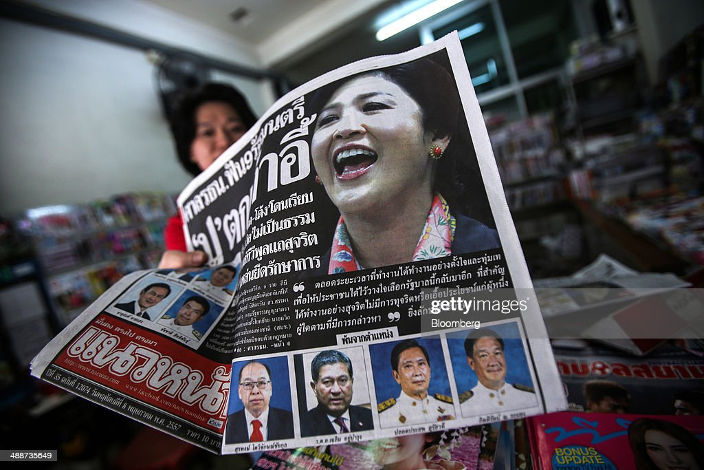 A vendor holds up a newspaper featuring ousted Prime Minister Yingluck Shinawatra on its front page at a newsstand in Bangkok, Thailand, on Thursday, May 8, 2014. The baht fell to a one-month low and stocks slumped on concern global investors will shun Thailand after a court ruling to remove Yingluck Shinawatra as prime minister worsened the nation's political crisis. Photographer: Dario Pignatelli/Bloomberg via Getty Images