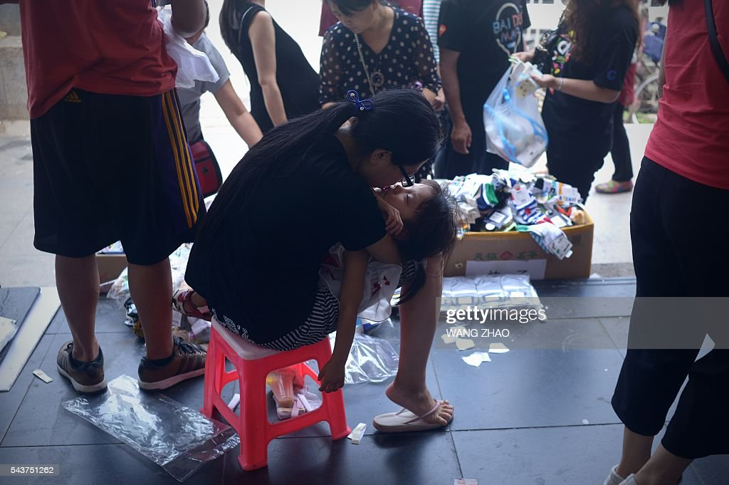 A vendor (C) kisses her daughter as she waits for customers along a sidewalk in Beijing on June 30, 2016. China's economic outlook is uncertain with corporate debt and an opaque financial sector contributing to looming vulnerabilities, an International Monetary Fund Official said on June 14. / AFP / WANG