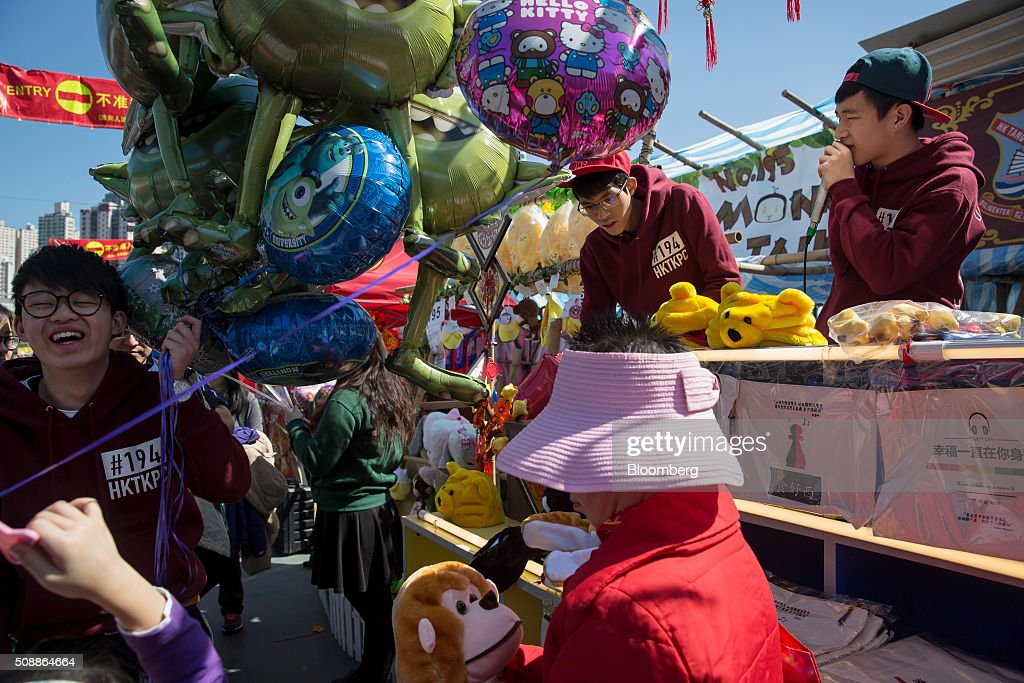 A vendor, left, holds balloons for sale at the Lunar New Year fair in Victoria Park in Hong Kong, China, on Sunday, Feb 7, 2016. The city's financial markets will close on Feb. 8 for the Lunar New Year holidays and resume trading on Feb. 11. Photographer: Billy H.C. Kwok/Bloomberg via Getty Images