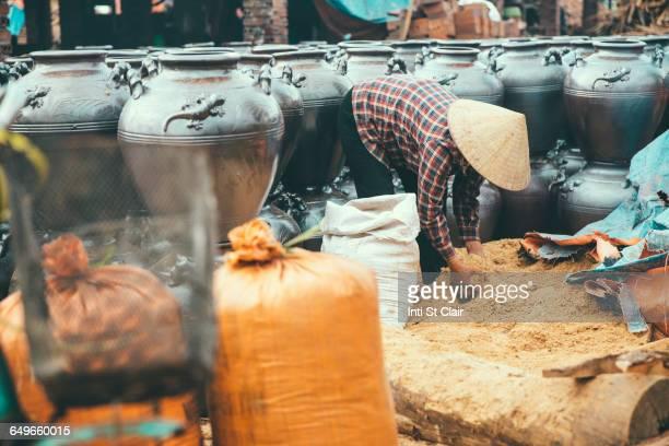 Vendor lifting grain into pots in market