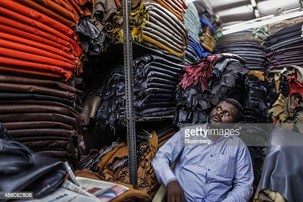 A vendor looks at rolls of leather at a store in the Dharavi slum area of Mumbai India on Saturday Aug 29 2015 India's benchmark stock index fell...