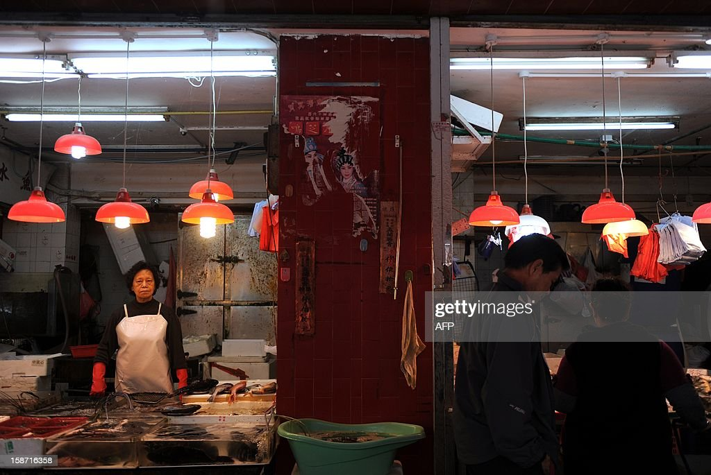 A vendor looks on as customers inspect fresh seafood at a wet market in Hong Kong on December 26, 2012. With the global economic weakness continuing to impact domestic economy, the IMF said it expects Hong Kong's economy to grow 1.25 percent this year, before rebounding to three percent next year. AFP PHOTO / Dale de la Rey