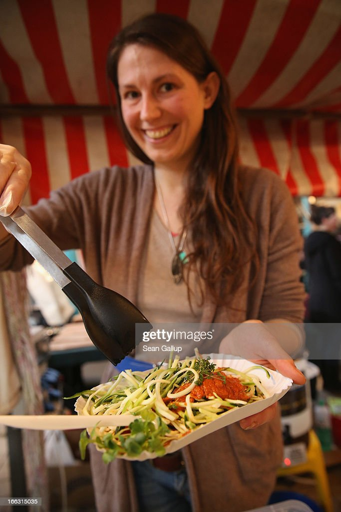 Vendor Melanie Lotos holds a plate of zucchini pasta with herb tomatoe and paprika sauce on the first day of Street Food Thursday at the Markthalle Neun market hall in Kreuzberg district on April 11, 2013 in Berlin, Germany. Street Food Thursday features sidewalk delicacies from a variety of culinary traditions and will be open every Thursday from 5 until 11. Berlin has become a major tourist destination in Europe and has developed a reputation as a hip, affordable and open-minded city.