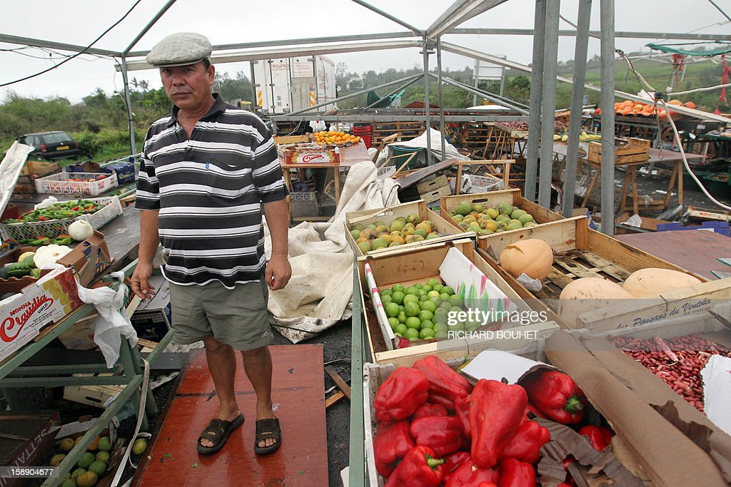 A vendor of fruits and vegetables poses as he discovers damages on his stalls, on January 3, 2013 in Saint-Gilles, western part of French overseas' island of La Reunion, after cyclone Dumile lashed Reunion. Winds of up to 180 kilometres per hour (110 miles per hour) and torrential rain caused extensive damage to the electricity network after cyclone Dumile passed within 90 kilometres of the island's west coast at around 0900 GMT. AFP PHOTO / RICHARD BOUHET
