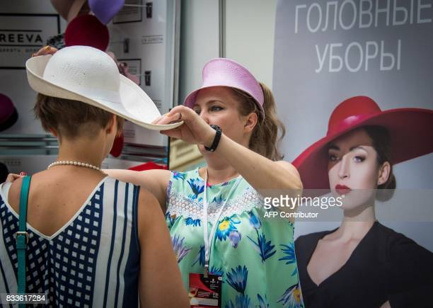 A vendor offers a hat to a client during the international fashion fair Chapeau Mosfur 2017 in Moscow on August 17 2017 / AFP PHOTO / Mladen ANTONOV