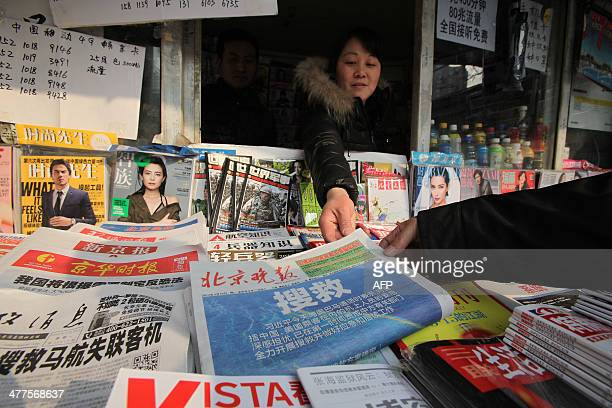 A vendor offers a newspaper with reports about the missing Malaysia Airlines flight to a customer in a news stand in Beijing on March 10 2014...