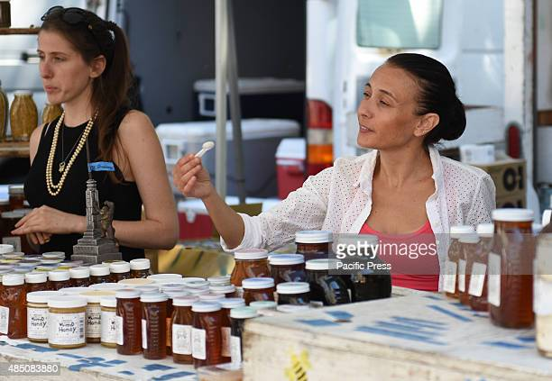 Vendor offers sample of wild honey to shopper Union Square Park greenmarket is one of New York City's largest and oldest dating back to 1976