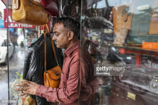 A vendor opens the door of a leather goods store in the Dharavi area of Mumbai India on Tuesday July 18 2017 India's new goods and services tax...