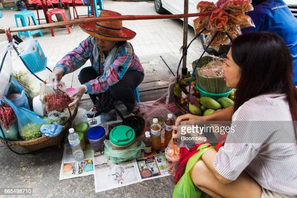 A vendor picks out chilli peppers at a food stall in the Phaya Thai District of Bangkok Thailand on Wednesday April 5 2017 The central...