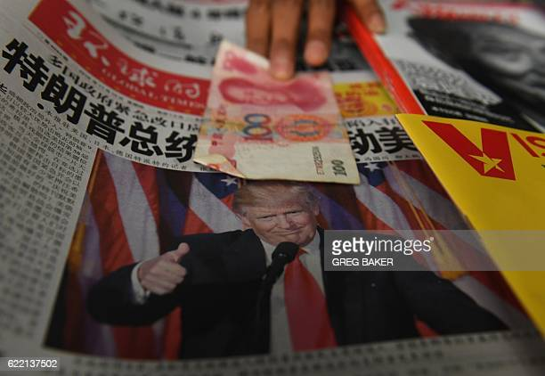TOPSHOT A vendor picks up a 100 yuan note above a newspaper featuring a photo of US presidentelect Donald Trump at a news stand in Beijing on...