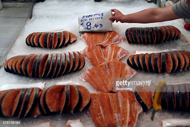 A vendor places a hand written euro price sign on a display of salmon fillets for sale at the Varvakeios fish and meat market in Athens Greece on...