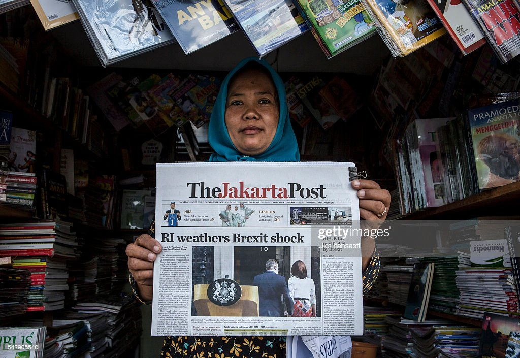 A vendor poses with the Indonesian newspaper The Jakarta Post which shows the cover headline which reads 'RI weathers Brexit shock', on June 25, 2016 in Yogyakarta, Indonesia. The results from the historic EU referendum has now been declared and the United Kingdom has voted to LEAVE the European Union.