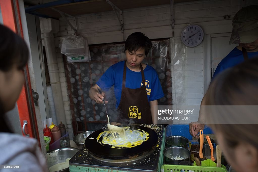 A vendor (C) prepares a traditional Chinese breakfast crepe to customers in Beijing on April 29, 2016. Chinese steel output rose in March, despite repeated pledges by the world's top producer to cut capacity as the worldwide industry languishes under a global glut. / AFP / NICOLAS