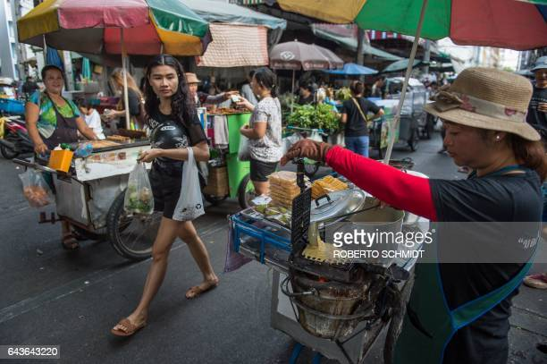 A vendor prepares a waffle on her street food cart at a local market in downtown Bangkok on February 22 2017 / AFP / ROBERTO SCHMIDT