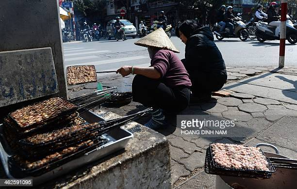 A vendor prepares 'bun cha' or grilled porc with noodle to sell at her open air street shop in downtown Hanoi on January 14 2014 Street food stalls...