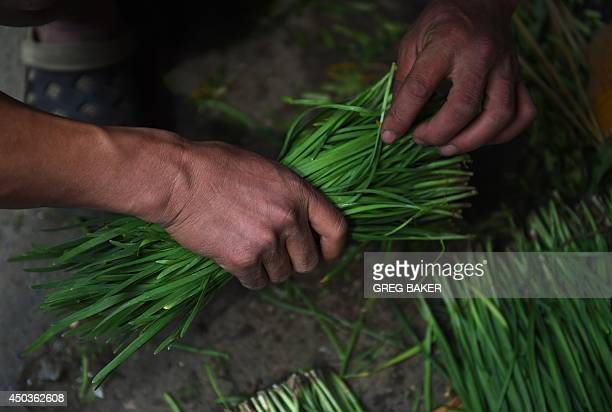 A vendor prepares chives for sale at an outdoor market in Beijing on June 10 2014 China's annual inflation rose sharply to 25 percent in May official...