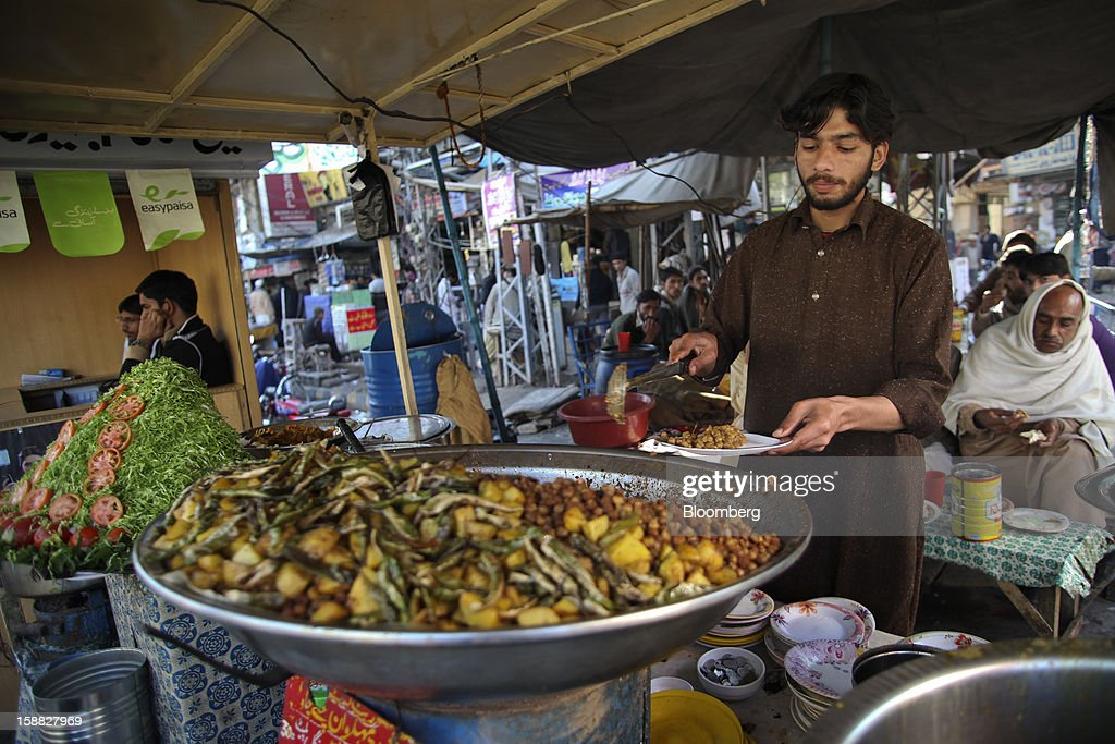 A vendor prepares food at a market in Rawalpindi, Pakistan, on Sunday, Dec. 30, 2012. Pakistan's economy will probably expand 3.5 percent in the 12 months through June, the International Monetary Fund forecast Nov. 29, less than the 4.3 percent predicted by the government. Photographer: Asad Zaidi/Bloomberg via Getty Images