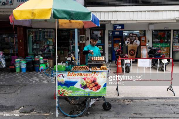 A vendor prepares grilled sausages and other meat snacks at a food stall in the Phaya Thai District of Bangkok Thailand on Wednesday April 5 2017 The...