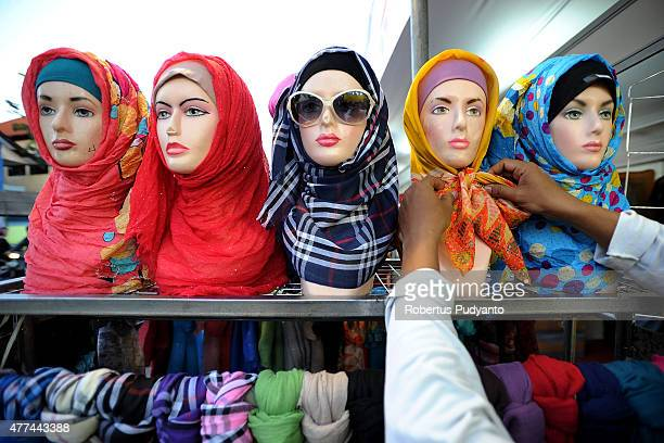 A vendor prepares hijabs for sale during Ramadan on June 17 2015 in Surabaya Indonesia Muslims worldwide observe Ramadan the ninth month of the...