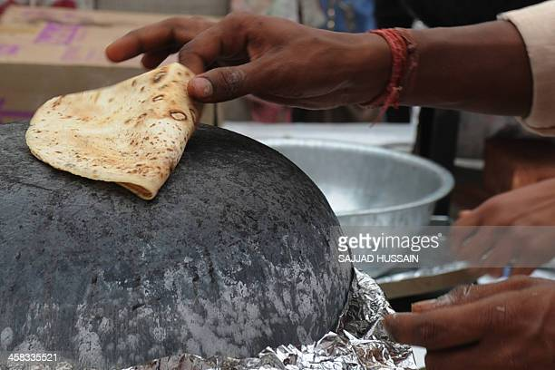 A vendor prepares roti during the National Street Food Festival at Jawaharlal Nehru Stadium in New Delhi on December 21 2013 Over 100 vendors are...