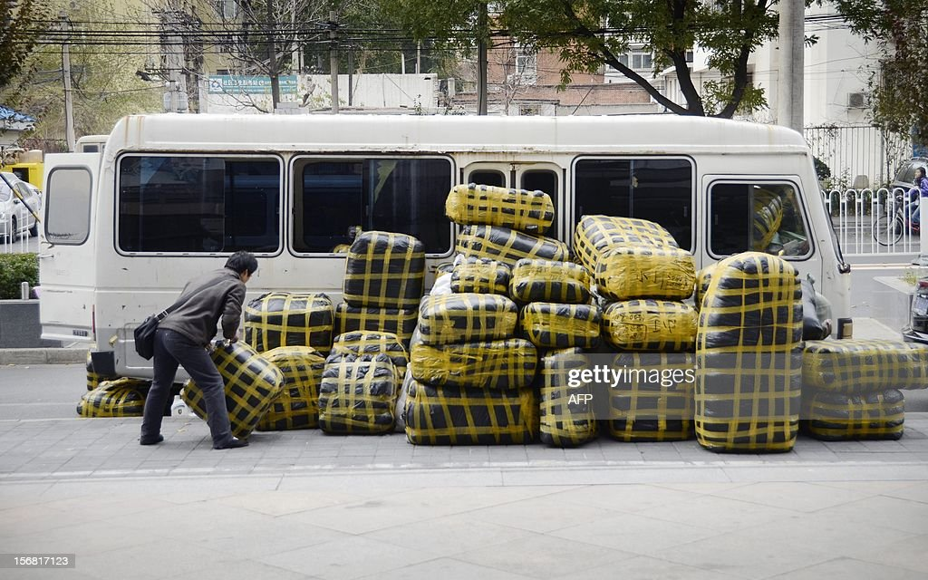 A vendor prepares to carry packages after unloading them from his vehicle in front of a market in Beijing on November 22, 2012. China's manufacturing activity grew in November for the first time in 13 months, HSBC said on November 22, in a further sign of strength in the world's second-largest economy after a marked slowdown.