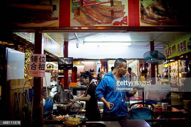 A vendor prepares to light a cigarette at a food stall in the Gongbei district of Zhuhai Guangdong province China on Saturday Nov 15 2014 Investors...