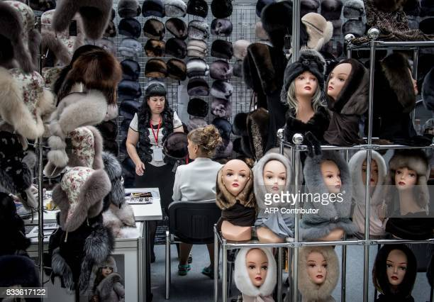 TOPSHOT A vendor presents a collection of fur hats during the international fashion fair Chapeau Mosfur 2017 in Moscow on August 17 2017 / AFP PHOTO...