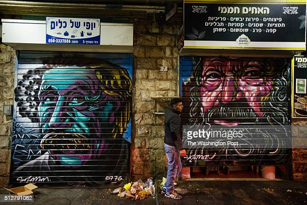 A vendor pulls down the shutter to a store next to graffiti depicting physicist Albert Einstein which was painted over a closed shutter of another...