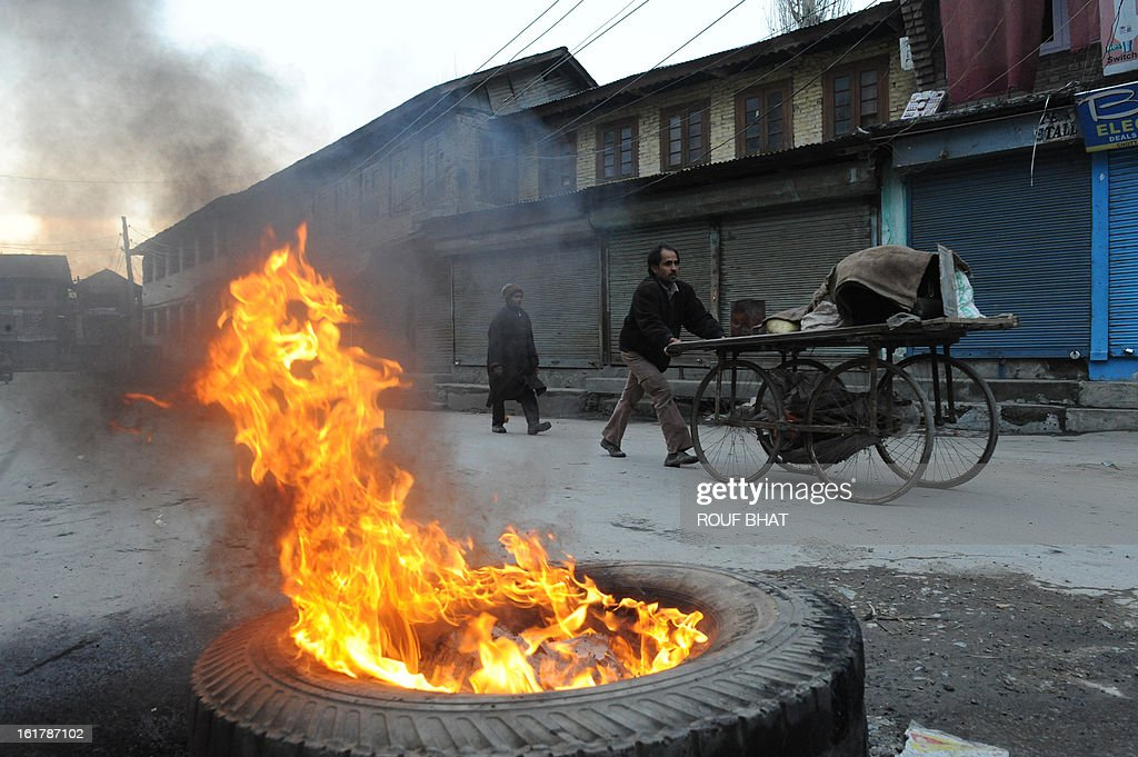 A vendor pushes his cart past a burning tyre set on fire by demonstrating youths during a strike in Srinagar on February 16, 2013. A curfew imposed in Indian Kashmir after the execution of a separatist convicted over a 2001 attack on parliament was lifted Saturday but a strike against the hanging paralysed the region. AFP PHOTO/ Rouf BHAT