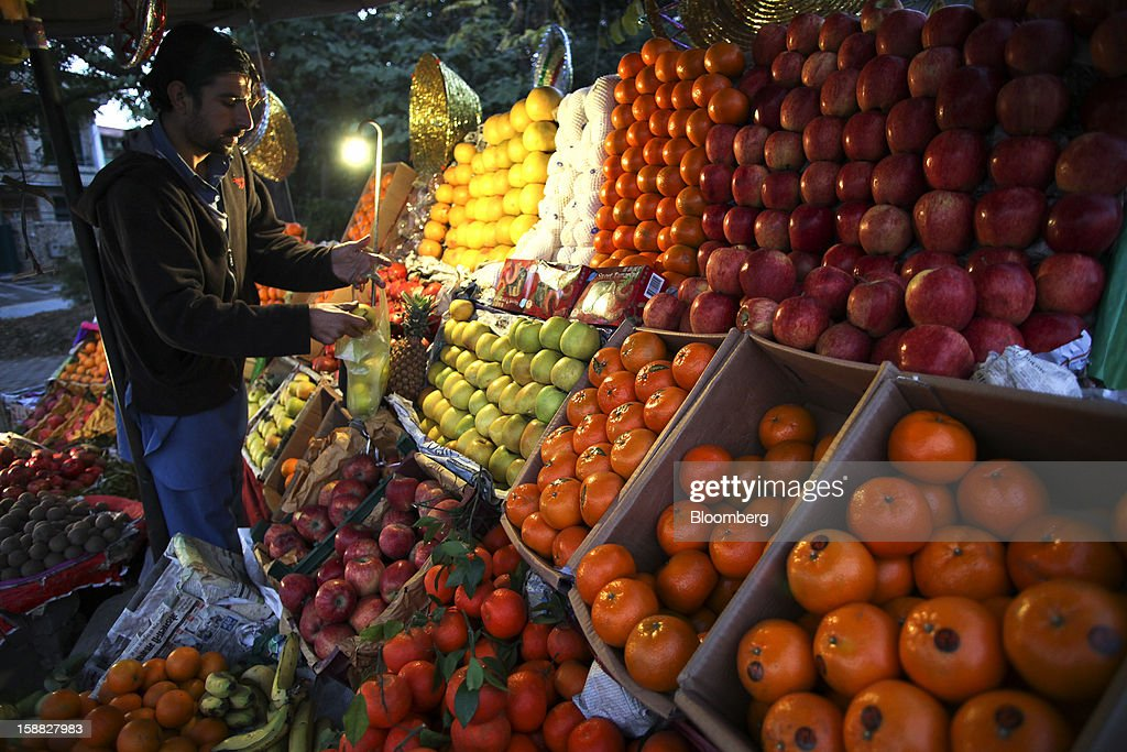 A vendor puts fruits in a plastic bag in Islamabad, Pakistan, on Sunday, Dec. 30, 2012. Pakistan's economy will probably expand 3.5 percent in the 12 months through June, the International Monetary Fund forecast Nov. 29, less than the 4.3 percent predicted by the government. Photographer: Asad Zaidi/Bloomberg via Getty Images
