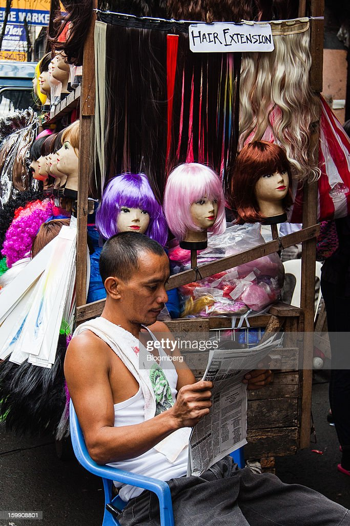 A vendor reads a newspaper as he sits in front of a stall selling wigs and hair extensions at the Divisoria market in Manila, the Philippines, on Tuesday, Jan. 22, 2013. Philippine government bonds advanced on speculation the central bank will hold its benchmark interest rate at a record low at a meeting tomorrow, supporting demand for the nation's debt. Photographer: Julian Abram Wainwright/Bloomberg via Getty Images