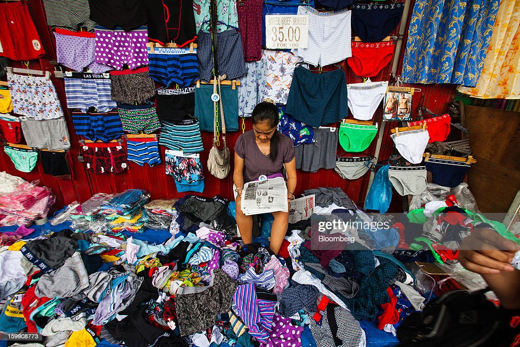 A vendor reads a newspaper as she waits for customers at her stall selling underwear at the Divisoria market in Manila, the Philippines, on Tuesday, Jan. 22, 2013. Philippine government bonds advanced on speculation the central bank will hold its benchmark interest rate at a record low at a meeting tomorrow, supporting demand for the nation's debt. Photographer: Julian Abram Wainwright/Bloomberg via Getty Images