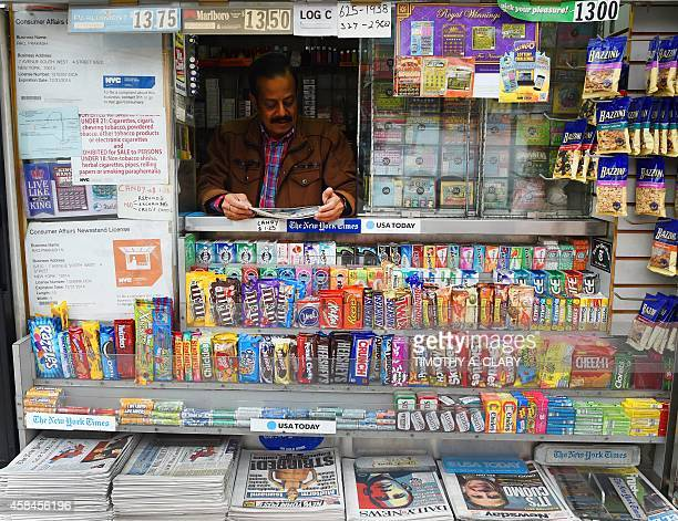 A vendor reads the front page news at his newstand in Grand Central Station in New York November 5 2014 the morning after Republicans took the Senate...