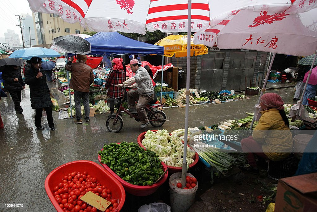 A vendor, right, sells vegetables at a market in Shanghai, China, on Thursday, Feb. 7, 2013. China's consumer prices rose 2 percent in January from a year earlier while the producer-price index dropped 1.6 percent, the National Bureau of Statistics said today in Beijing. Photographer: Tomohiro Ohsumi/Bloomberg via Getty Images
