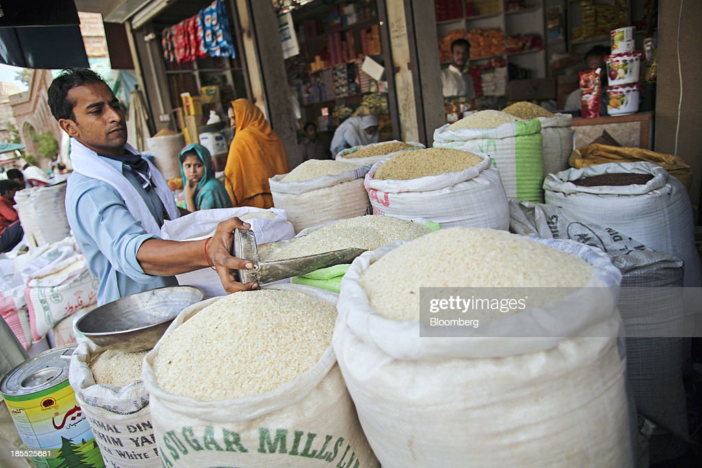 A vendor scoops a measure of rice from a bag at a market in the district of Faisalabad in Punjab, Pakistan, on Sunday, Oct. 13, 2013. Prime Minister Nawaz Sharifs four-month-old government is struggling to revive the $231 billion economy crippled by chronic energy shortages and a spike in violence from a Taliban insurgency in the northwest. Photographer: Asad Zaidi/Bloomberg via Getty Images