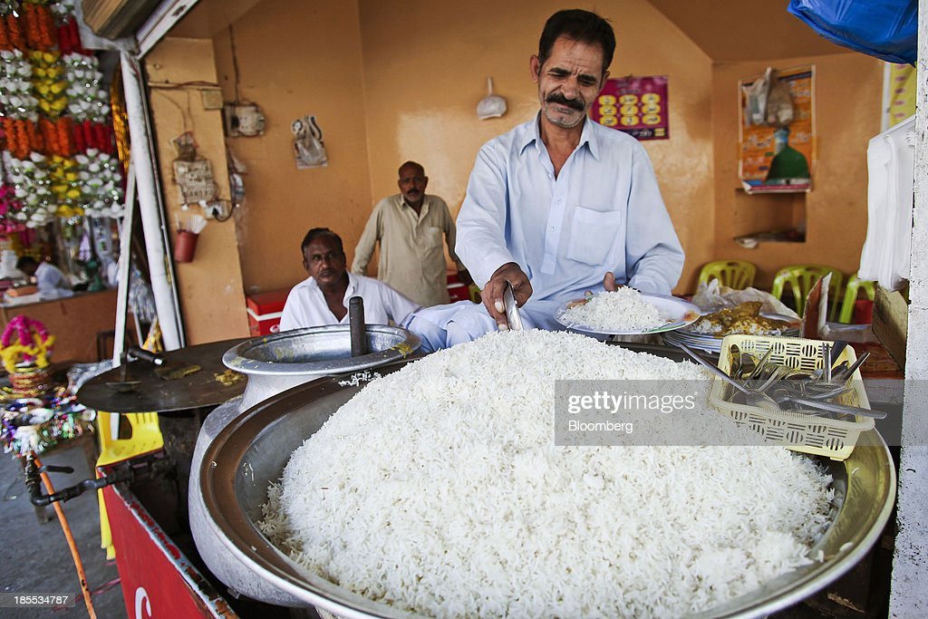 A vendor scoops rice onto a plate at a market in the district of Faisalabad in Punjab, Pakistan, on Sunday, Oct. 13, 2013. Prime Minister Nawaz Sharifs four-month-old government is struggling to revive the $231 billion economy crippled by chronic energy shortages and a spike in violence from a Taliban insurgency in the northwest. Photographer: Asad Zaidi/Bloomberg via Getty Images