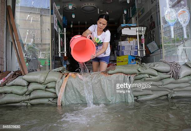 A vendor scoops water out of her flooded shop in South Lake Community of Wuhan Hubei Province of China on 7 July 2016